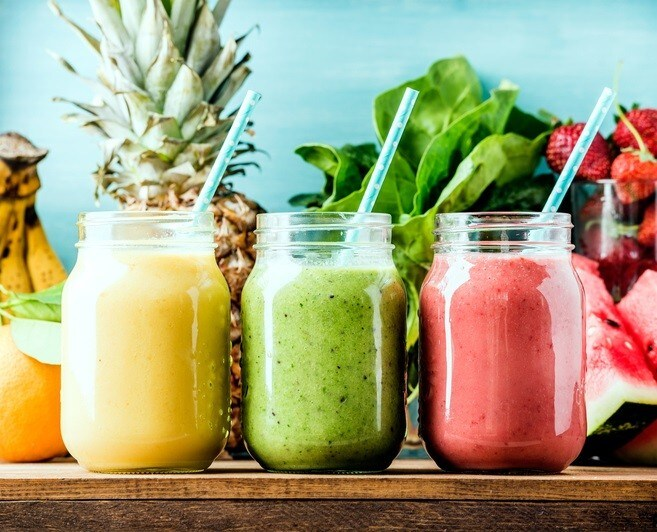 Freshly blended fruit smoothies of various colors and tastes  in glass jars. Yellow, red, green. Turquoise blue background