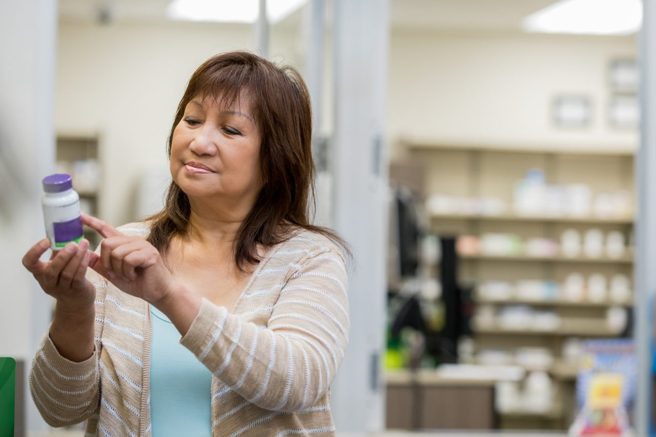 Senior adult Asian American woman is reading the label of a pill bottle while shopping for medicine in a local pharmacy.